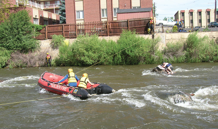 Firefighters use a tethered inflatable boat to reach a victim stranded in swift water. (Photos 1-2 courtesy of Dive Rescue International.)