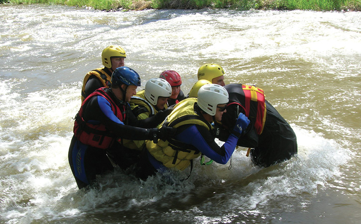 A wade crew of rescuers snatches a victim from swift water and walks him to safety on shore.