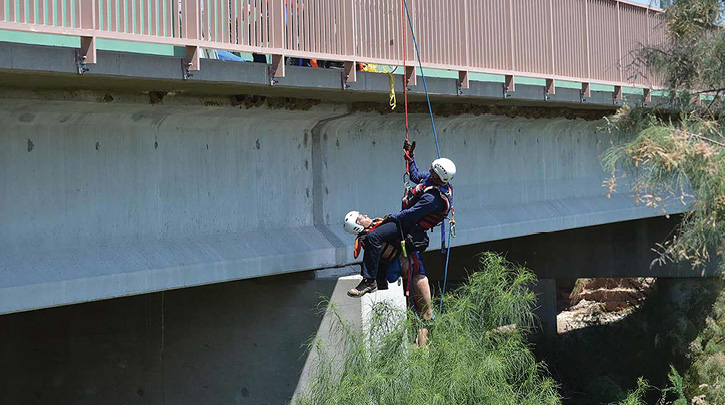 A Northwest (AZ) Fire District  firefighter pulls a simulated victim from a swift water situation after rappelling off a bridge to reach the victim. (Photos 3-4 courtesy of Northwest Fire Department.)