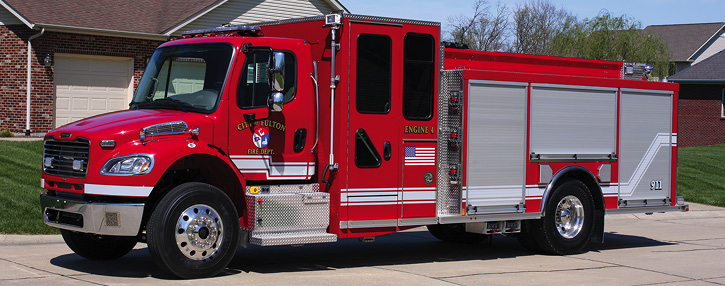 The Fulton (MO) Fire Department operates an all-red two-door Freightliner with a standalone Rosenbauer Smart Cab, 1,500-gpm rear-mount pump, 750-gallon tank, and unpainted roll-up doors.