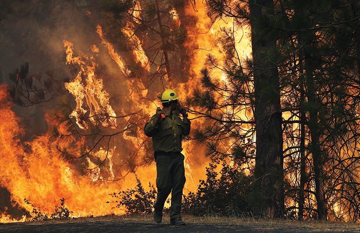 A wildland firefighter uses a BK Technologies KNG2 portable radio to communicate with the incident commander.
