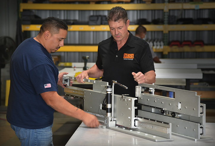 OnScene Solutions founder and general manager Clay Horst, right, works with production lead Junior Sanchez, left, on fine-tuning the company's new X-30 cargo lift system.