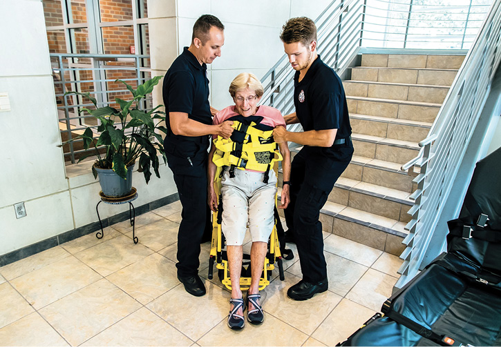 Two medics use a Binder Lift to lift a patient from a stair chair.