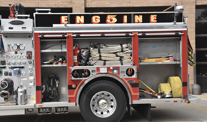 The driver's side with 2½-inch roll-ups, fittings, a 50-foot section of five-inch hose, an SCBA for the driver, and spare SCBA cylinders.