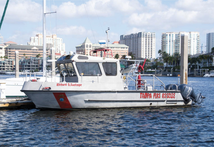 Tampa operates the Richard D. Santmyer, a 32-foot aluminum Sea Ark with an enclosed wheelhouse, carrying a 1,250-gpm pump, a patient transport area for a Stokes basket on deck, and a fold-down dive door with attached ladder.